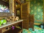 Villa: Bathroom free form marble sink, antique batik wall hanging.