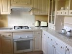 Country kitchen with washer dryer, convection oven, gas hob and extractor fan, intergral fridge.