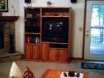 Living room showing entertainment center with fireplace on left and balcony door on right
