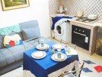 Divano, lavatrice, piano cottura e tavolo da pranzo