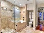 Large and luxurious tub and travertine shower has old world charm.