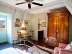 There is an old walnut armoire, comfy easy chair - also a table for two.