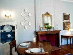 The handsome oval dining table sits in front of the early 19th century fireplace.