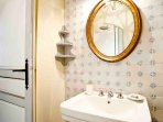 A separate bathroom has a shower and handsome handmade tiles.