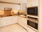 Gourmet kitchen with Wolf appliances, Subzero refrigerator, granite countertops, & travertine floors
