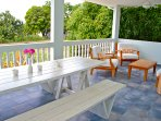 Outdoor dining and lounge area under covered patio.  Excellent ocean views.