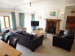 Comfortable living/dining room with log burner, arch to kitchen.