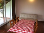 Zona salita-comedor con sofá cama y mesa con cuatro sillas