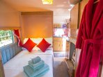 Small double bed that folds away into a cupboard during the day. Luxury robes, towels  & toiletries.