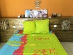 le lit moderne avec ses apliques en bois flotté du pays