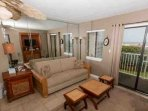 Tiled living room with area rug, occasional tables, end table with lamp, ceiling fan and sofa