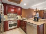 The gourmet chef's fully equipped kitchen boasts a full array of stainless-steel appliances, cherry wood cabinetry...
