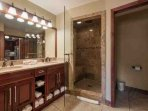 The master bathroom features an oversized jetted tub, granite counters, two vanities, steam and rainfall shower, and a...