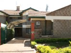 front of townhouse property with gate wide open; within the gated community; carport with canopy