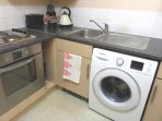A fully equipped kitchen with kettle, toaster and washing machine.