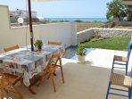 Veranda esclusiva con tavolo da pranzo, vista sul mare e sul giardino