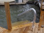 Stairs that step into crystal clear water with sandy bottom