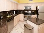 Fully equipped kitchen with stainless steel appliances and granite counters