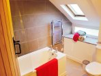 Modern and bright tiled bathroom with shower over bath