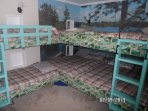 Ladders lead to upper bunks in kids' bunk room.  Stocked with toys.