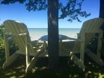 Double adirondack chairs looking out on Lake Huron