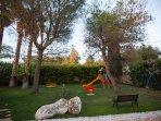 Parco giochi con altalene, scivolo, girella e giochi a molla