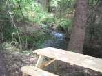 Picnic table by the year round stream that runs along the edge of this 5 acre property.