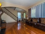 The honey glow of the original heart pine floor points you to the beauty  of the fireplace mantle