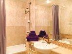 Bathroom: Shower over bath, toilet, bidet, sink, mirrored wall, hairdryer