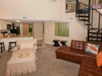 Carpeted living room with chair/ottoman and spiral staircase to loft