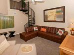 Sectional sofa, ceiling fan and spiral staircase to loft