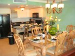 Luxurious 6-seat dining table adjacent to modern open kitchen.