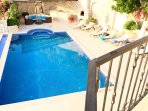 Large pool with jacuzzi, barbecue for al fresco meals, outdoor kitchen and bar, soft seating area.