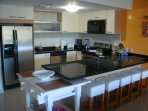 Full-size fully equipped kitchen with bar table.
