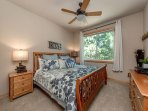 Master bedroom with a king size bed and ceiling fan above!