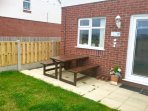 Enclosed back garden with picnic table.