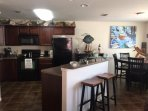 Kitchen with attached dining room, 6 seat table, 2 seat bar stools, microwave, kitchen utensils