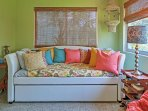 This quaint daybed in the sunroom serves as an additional sleeping arrangement for 2 extra guests