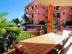 Terrace with table and chairs and direct access to pool and beach