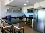 Full-size fully equipped modern kitchen with breakfast/bar table.