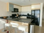 Full-sized fully equipped modern kitchen with 4-seat dining bar-table.