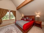 Romantic master suite with King-sized bed, vaulted ceiling and exposed wood beams