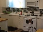 New kitchen with gas stove and microwave. Utensils,pots and pans,and dish ware included.