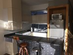 Open kitchen, fridge, microwave and oven.