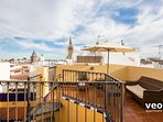 Private terrace with outdoor furniture. The tower bell at the far end is La Giralda.