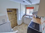 A stripped pine door leads from the living room to the fitted kitchen