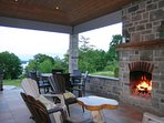 Covered patio with outdoor wood burning fireplace, room for dining and lounging, firewood included