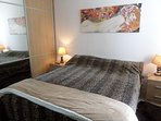 1 bedroom with king bed with good mattress, bed side tables with lights, cupboard with mirror