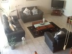 View of lounge, beautiful leather suite, cool tiled floor.