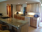 Recently renovated kitchen with granite countertops and built-in grill.